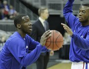 Kansas guards Tyshawn Taylor, left,  and Naadir Tharpe warm up before tipping off against Davidson on Monday, Dec. 19, 2011 at Sprint Center in Kansas City, Mo.