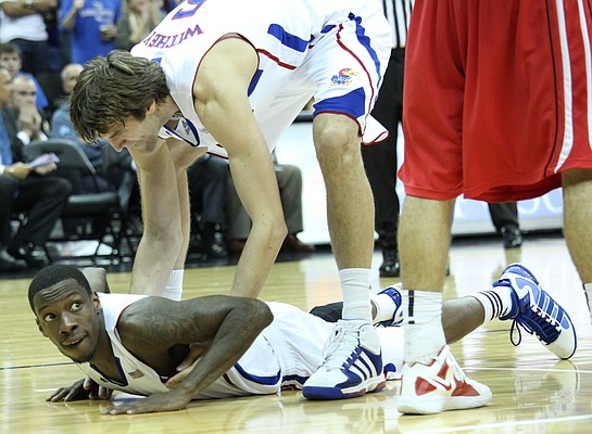 Kansas center Jeff Withey helps up teammate Tyshawn Taylor after Taylor was fouled in second half against Davidson on Monday, Dec. 19, 2011 at Sprint Center in Kansas City, Mo.