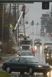 Workers with Wright Tree Service deal with rain and traffic as they trim trees near the intersection of 23rd Street and Massachusetts St. Monday, Dec. 19, 2011. Westar has contracted with Wright to trim back trees near power lines in the city.