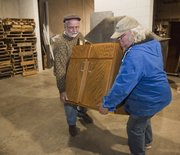 Sam Pepple, left, helps Byron James of Lawrence Habitat ReStore load a base cabinet Tuesday afternoon. KU's surplus program has delivered its 10,000th item to charity while helping to clear out old office furniture from various departments on campus.