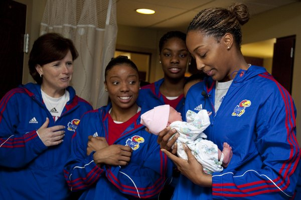 Kansas University women's basketball coach Bonnie Henrickson, CeCe Harper and Chelsea Gardner watch as Carolyn Davis holds newborn Colleen Kay Steadham during a visit with her parents, Shanna and Chris Steadham of Lawrence, on Tuesday, Dec. 21, 2011, at Lawrence Memorial Hospital.