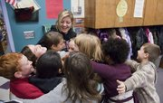 Woodlawn Elementary School third-grade teacher Lori Sinclair, center, is surrounded by her students in a group hug after she was awarded Wednesday with the Lawrence Schools Foundation annual $5,000 Dedication to Education Award.