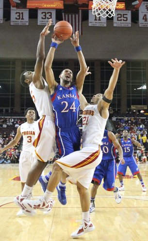 Kansas guard Travis Releford is fouled on the shot as he splits USC defenders Byron Wesley, left, and Aaron Fuller during the first half on Thursday, Dec. 22, 2011 at the Galen Center.