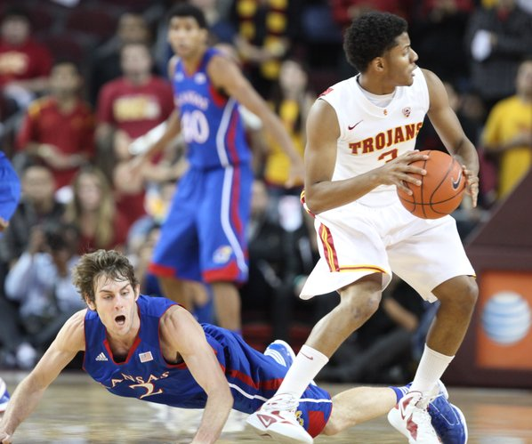 Kansas guard Conner Teahan loses his footing going for a loose ball with USC guard Alexis Moore during the first half Thursday, Dec. 22, 2011 at the Galen Center in Los Angeles, Calif.