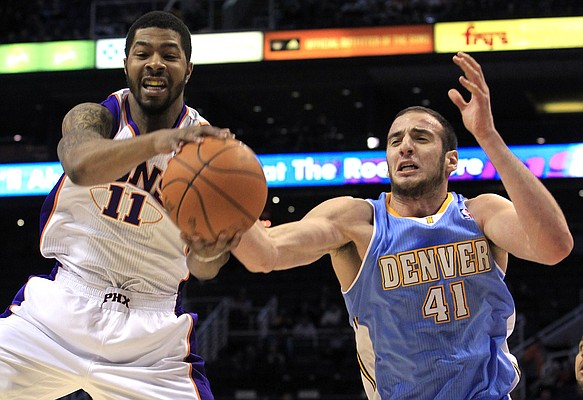 Phoenix Suns' Markieff Morris (11) pulls down a rebound in front of Denver Nuggets' Kosta Koufos (41) during the first quarter in a preseason NBA game Thursday, Dec. 22, 2011, in Phoenix.