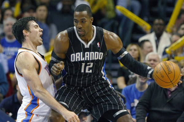 Orlando Magic's Dwight Howard (12) drives to the basket against Oklahoma City Thunder's Nick Collison, left, during the third quarter of an NBA basketball game in Oklahoma City, Sunday, Dec. 25, 2011. The Thunder won 97-89.