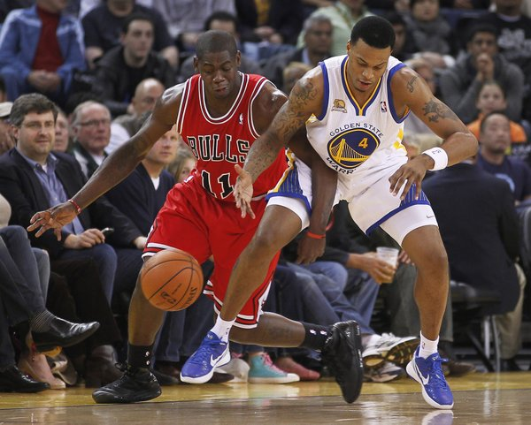 Chicago Bulls' Ronnie Brewer (11) vies for a loose ball with Golden State Warriors' Brandon Rush (4) during the first half of an NBA basketball game Monday, Dec. 26, 2011, in Oakland, Calif.