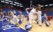 "Kansas guard Travis Releford gets down for ""hound dog pushups"" next to 8-year-old Tyler Peterson, left, Topeka, on Tuesday, Dec. 27, 2011, during the Holiday Hoops Clinic at Allen Fieldhouse. The pushups, which were ordered by director of basketball operations, Barry Hinson, consisted of lifting one&squot;s head up and howling like a dog."