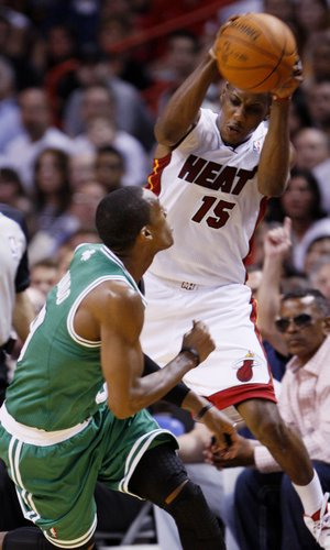 Miami Heat guard Mario Chalmers (15) attempts to keep the ball in bounds as he is guarded by Boston Celtics guard Rajon Rondo during the first half of an NBA basketball game, Tuesday, Dec. 27, 2011, in Miami.