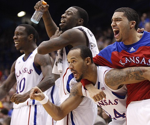 Kansas players Travis Releford, bottom front, Niko Roberts, right, Elijah Johnson and Tyshawn Taylor go wild as center Jeff Withey is fouled on a dunk during the second half against Howard on Thursday, Dec. 29, 2011 at Allen Fieldhouse.