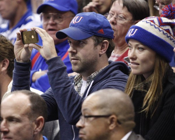 Actor and Kansas native Jason Sudeikis shoots a picture of the Kansas huddle next to his guest, actress Olivia Wilde, during the second half on Thursday, Dec. 29, 2011 at Allen Fieldhouse.