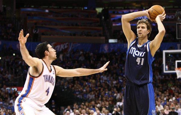Dallas Mavericks forward Dirk Nowitzki (41) looks to pass as Oklahoma City Thunder's Nick Collison (4) defends during the first quarter of an NBA basketball game in Oklahoma City, Thursday, Dec. 29, 2011.