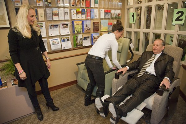 Lawrence businessman Miles Schnaer tries out one of two infusion chairs to see which one is most comfortable in the waiting room of the Lawrence Memorial Hospital's Oncology Center, while friends Aimee Jackson, left, and Kelli Alldredge await to hear the results. The trio are board members of Jamie's Wish Foundation, which was created in memory of Jamie Pursley, who died last March from cancer. Her dying wish was to upgrade the 15 infusion rooms at LMH and these three helped make her dream come true. They've raised the $100,000 needed, and one of the infusion chairs will replace the old ones. They are having staff, patients and visitors vote on their favorite, so far the one on the left is winning.