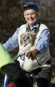 """Marcia Runyon, Weatherby Lake, Mo., bicycles with her granddaughter's family dog, Otis, on Saturday at the end of a six-mile ride on the levee trial in North Lawrence. Runyon and her husband, Norm, were visiting relatives in Lawrence on an unseasonably warm last day of the year. """"It's beautiful,"""" Runyon said."""