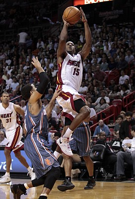 Miami Heat's Mario Chalmers (15) goes up to the basket against Charlotte Bobcats' D.J. Augustin, foreground, in the first half of an NBA basketball game in Miami, Sunday, Jan. 1, 2012.