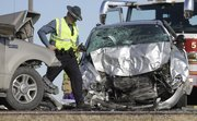 A Kansas Highway Patrol trooper inspect the scene of an accident that sent five people to the hospital Tuesday, Jan. 3, 2012 on Kansas Highway 56.
