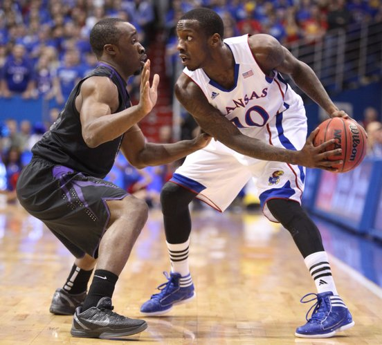 Kansas guard Tyshawn Taylor looks to make a move against Kansas State guard Martavious Irving during the first half on Wednesday, Jan. 4, 2012 at Allen Fieldhouse.