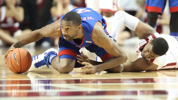 Kansas forward Justin Wesley chases down a loose ball with Oklahoma guard Steven Pledger during the first half Saturday, Jan. 7, 2012, at Lloyd Noble Center.