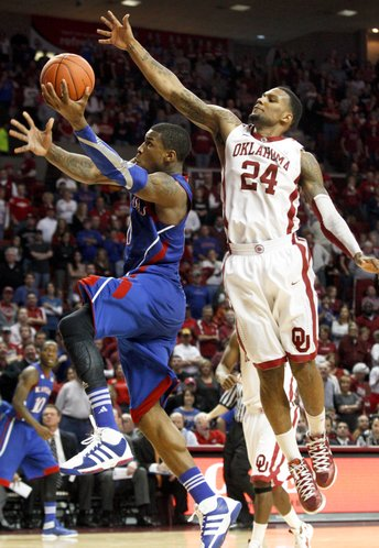 Kansas forward Thomas Robinson ducks under Oklahoma forward Romero Osby for a bucket during the second half Saturday, Jan. 7, 2012, at Lloyd Noble Center.