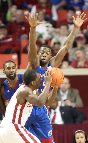 Kansas guard Elijah Johnson comes over the top of Oklahoma guard Sam Grooms during the second half Saturday, Jan. 7, 2012, at Lloyd Noble Center. At left is KU forward Justin Wesley.