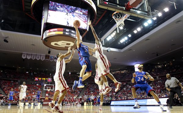 Kansas guard Conner Teahan elevates for a bucket between several Oklahoma defenders during the first half Saturday, Jan. 7, 2012, at Lloyd Noble Center.