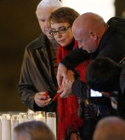 U.S. Rep. Gabrielle Giffords, and her husband, former astronaut Mark Kelly, light a candle during a memorial vigil remembering the victims and survivors one year after a gunman shot the Arizona congresswoman and killed six others, Sunday, Jan. 8, 2012, in Tucson, Ariz.