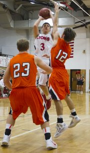 Lawrence High guard Jake Mosiman (3) shoots a pull-up jumper over Shawnee Mission Northwest guard Blake Evans (12) on Tuesday, Jan. 10, 2012, at LHS.