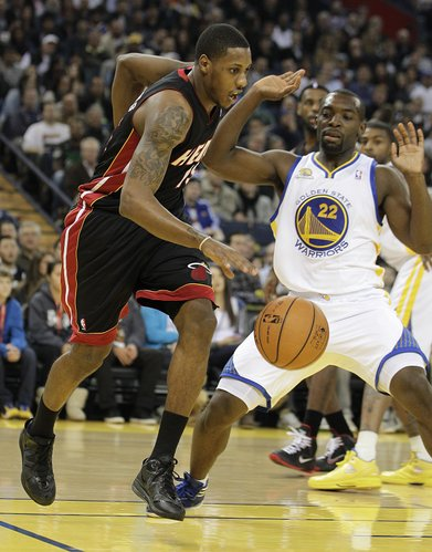 Miami Heat's Mario Chalmers, left, drives the ball past Golden State Warriors' Charles Jenkins (22) during the first half of an NBA basketball game, Tuesday, Jan. 10, 2012, in Oakland, Calif.