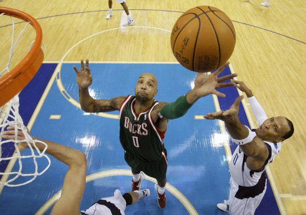 Milwaukee Bucks forward Drew Gooden (0) goes up for an offensive rebound against Dallas Mavericks forward Shawn Marion, right, in the first half of an NBA basketball game Friday, Jan. 13, 2012, in Dallas.