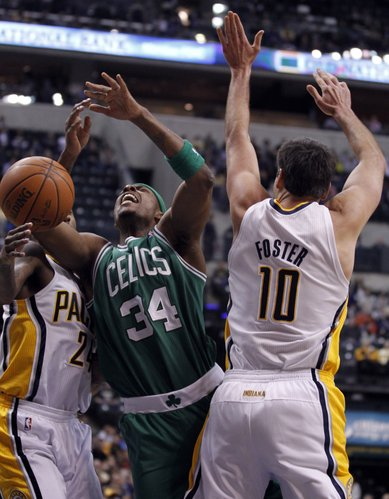Boston Celtics forward Paul Pierce, center is fouled as he shoots between Indiana Pacers guard Paul George, left, and center Jeff Foster in the first half of an NBA basketball game in Indianapolis, Saturday, Jan. 14, 2012.