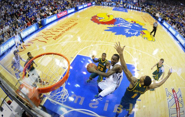Kansas guard Tyshawn Taylor dips under Baylor forward Perry Jones for a bucket during the second half on Monday, Jan. 16, 2012 at Allen Fieldhouse.