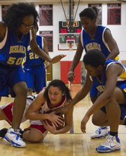 Lawrence High sophomore Kionna Coleman, center, beats Tyliese Wallace (50) and Alicia Terrell, right, to the floor to cover a loose ball during Lawrence High's game against KC Schlagle Tuesday, Jan. 17, 2012 at LHS.