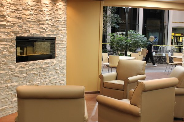 Lawrence Memorial Hospital's dining area, which is located on the lower level, features a fireplace, comfy chairs and opens up to the atrium.