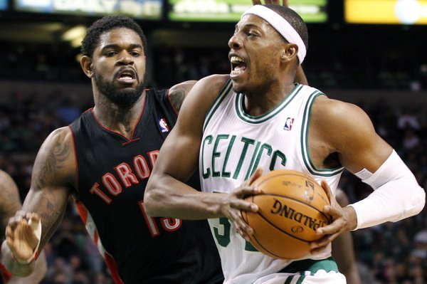 Boston Celtics forward Paul Pierce (34) drives past Toronto Raptors forward Amir Johnson (15) in the second quarter of an NBA basketball game in Boston, Wednesday, Jan. 18, 2012.
