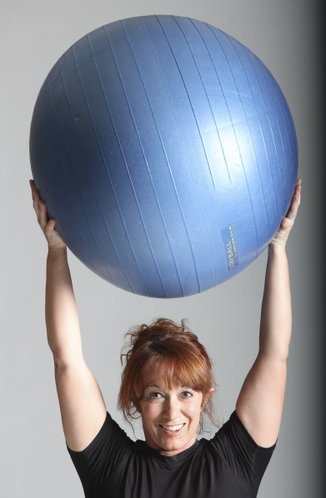 A squat with a stability ball held above the head.