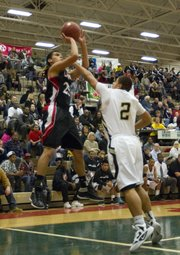 With Raymond Solis' (2) hand in his face, Lawrence High senior Anthony Buffalomeat, left, shoots a jumper during Lawrence High's game against Topeka High in the Topeka Invitational Friday, Jan. 20, 2012 in Topeka.
