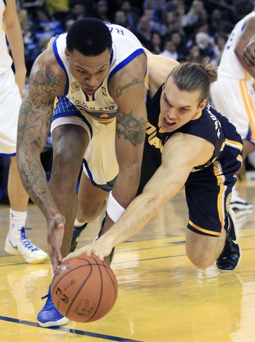 Indiana Pacers' Louis Amundson (17) battles for a loose ball against Golden State Warriors' Brandon Rush (4) during the first half of an NBA basketball game in Oakland, Calif., Friday, Jan. 20, 2012.