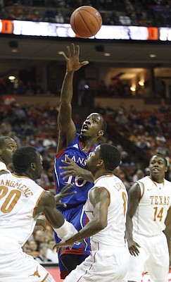 Kansas guard Tyshawn Taylor tosses up a lob over the Texas defense for teammate Thomas Robinson during the first half on Saturday, Jan. 21, 2012 at the Frank Erwin Center.
