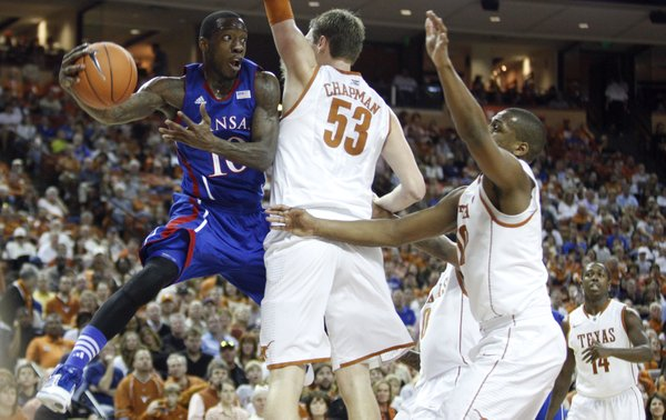 Kansas guard Tyshawn Taylor hooks around Texas big men Clint Chapman (53) and Jonathan Holmes (10) for a pass during the second half on Saturday, Jan. 21, 2012 at the Frank Erwin Center.