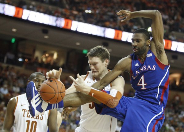 Kansas forward Justin Wesley wrestles for a loose ball with Texas center Clint Chapman during the second half on Saturday, Jan. 21, 2012 at the Frank Erwin Center.
