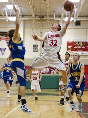Lawrence High senior Logan Henrichs (32) hangs in the air as he lofts a shot over Connor Soukup during Lawrence High's game against Olathe South Saturday, Jan. 21, 2012 in Topeka.
