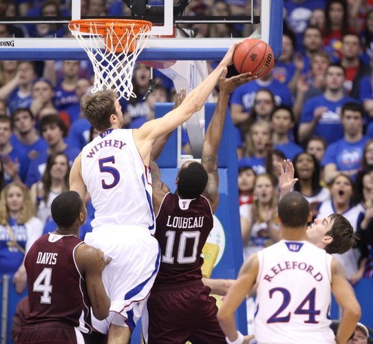 Kansas center Jeff Withey stuffs a shot by Texas A&M forward David Loubeau during the second half on Monday, Jan. 23, 2012 at Allen Fieldhouse.