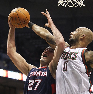 Milwaukee Bucks' Drew Gooden (0) blocks the shot by Atlanta Hawks' Zaza Pachulia during the first half of an NBA basketball game Monday, Jan. 23, 2012, in Milwaukee.