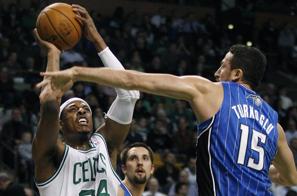 Boston Celtics small forward Paul Pierce (34) tries to shoot as Orlando Magic forward Hedo Turkoglu (15) reaches to block during the first quarter of an NBA basketball game in Boston, Monday, Jan. 23, 2012.