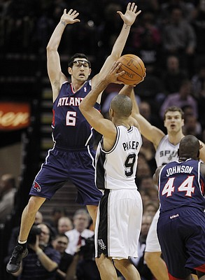 San Antonio Spurs' Tony Parker (9), of France, shoots over Atlanta Hawks' Kirk Hinrich (6)during the second half of an NBA basketball game on Wednesday, Jan. 25, 2012, at the AT&T Center in San Antonio. San Antonio won 105-83.