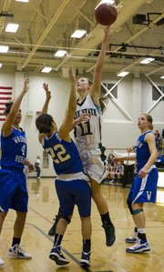 Surrounded by defenders, Free State junior Kennedy Kirkpatrick (11) hits the game-winning shot over Washburn Rural's Alycia Garcia (22) during Free State's semifinal game against Washburn Rural in the Firebird Winter Classic Friday, Jan. 27, 2012 at FSHS.