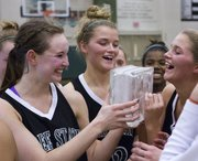 Free State's Kennedy Kirkpatrick, left, Chelsea Casady, center, and Abbey Casady smile as they hold the championship trophy after the championship game of the Firebird Winter Classic Saturday, Jan. 28, 2012, at FSHS. The Firebirds held on for a 54-50 victory