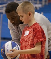 Camper Devin Hastings receives some one-on-one coaching from Elijah Johnson during the 28th annual Wilt Chamberlain Basketball Clinic held Sunday, Jan. 29, 2012, in Allen Fieldhouse. The clinic gives Special Olympians a chance to work with the Kansas men's basketball team in a variety of drills including shooting, passing and dribbling.