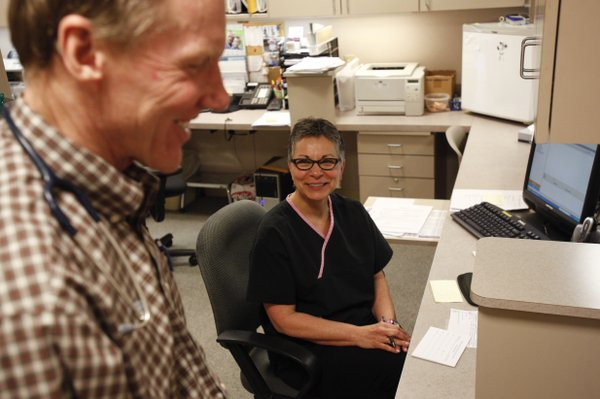 Dr. Rod Barnes stops by the desk of Joni Lawrence, a registered nurse who has worked with Barnes since 1980. Barnes credits Lawrence for keeping his practice together during his absence.