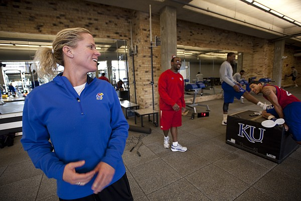 Andrea Hudy turns over her shoulder to laugh with players Thomas Robinson, Niko Roberts and assistant strength and conditioning coach Glenn Cain during a workout session. Nick Krug/Journal-World Photo